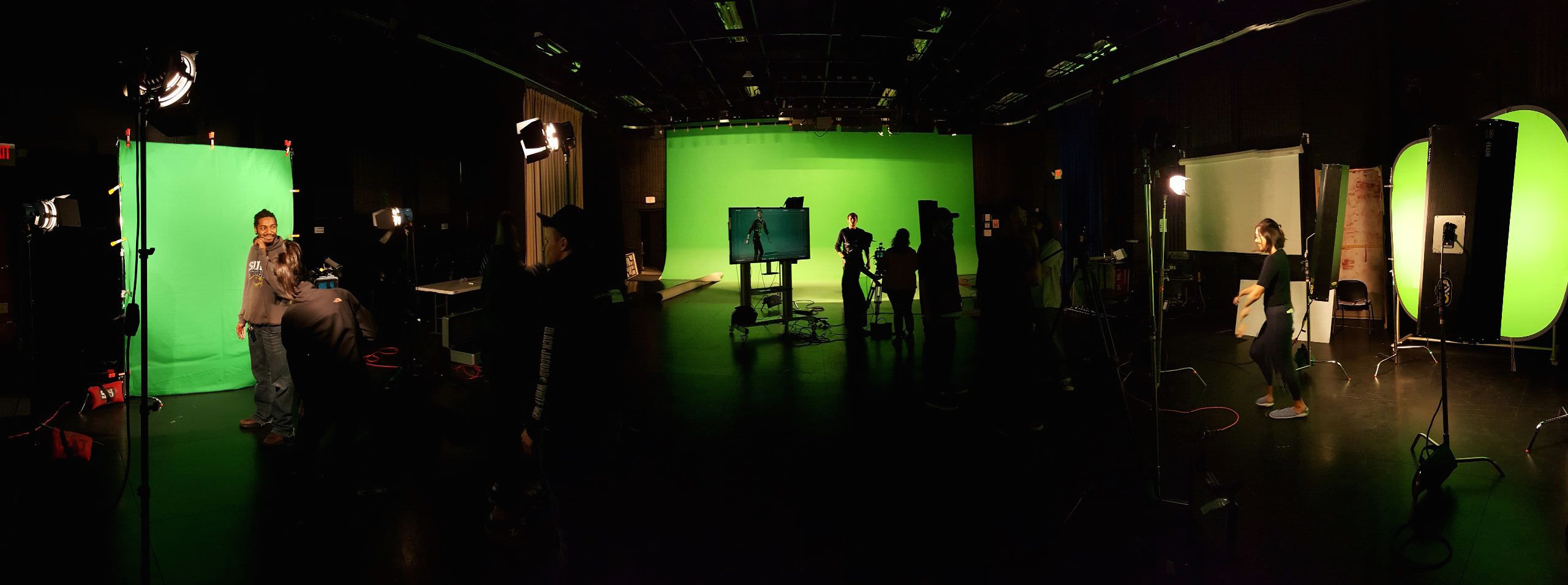 Cinematic Arts studio with students working with green screen and lighting.