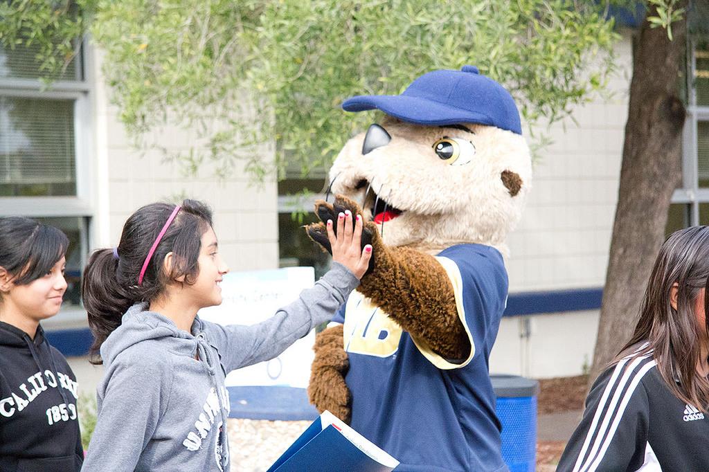 Middle school girl high-fiving CSUMB mascot Monte Rey