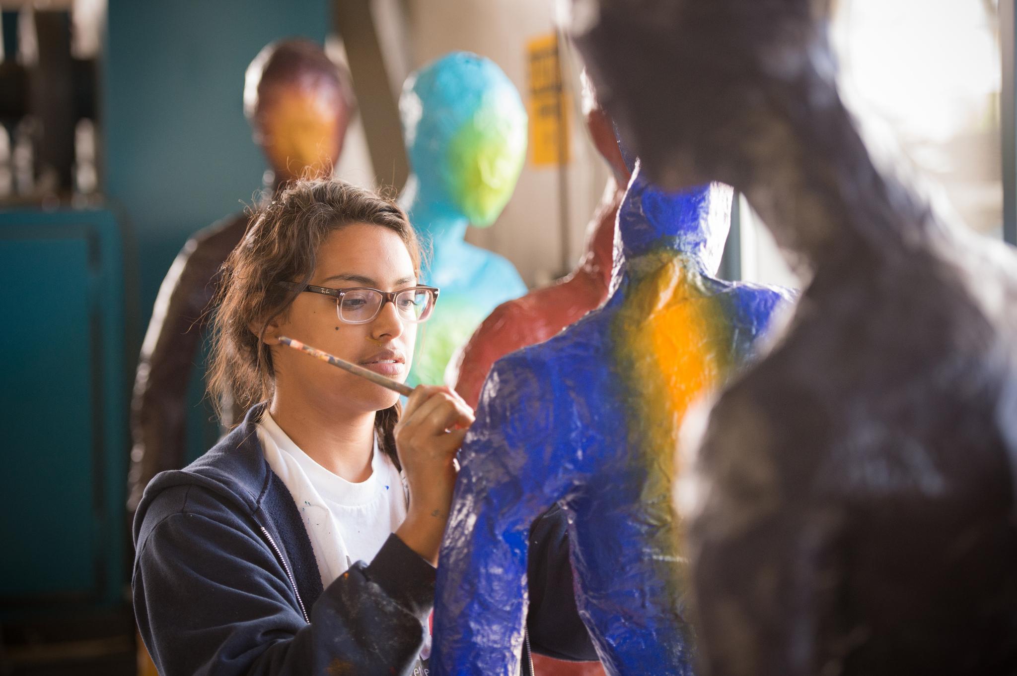 Art student working on capstone sculpture