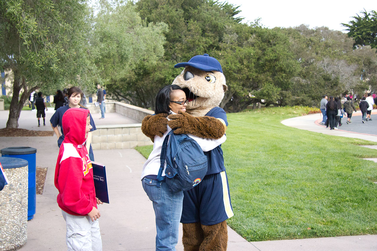 A parent hugs CSUMB mascot Monte Rey