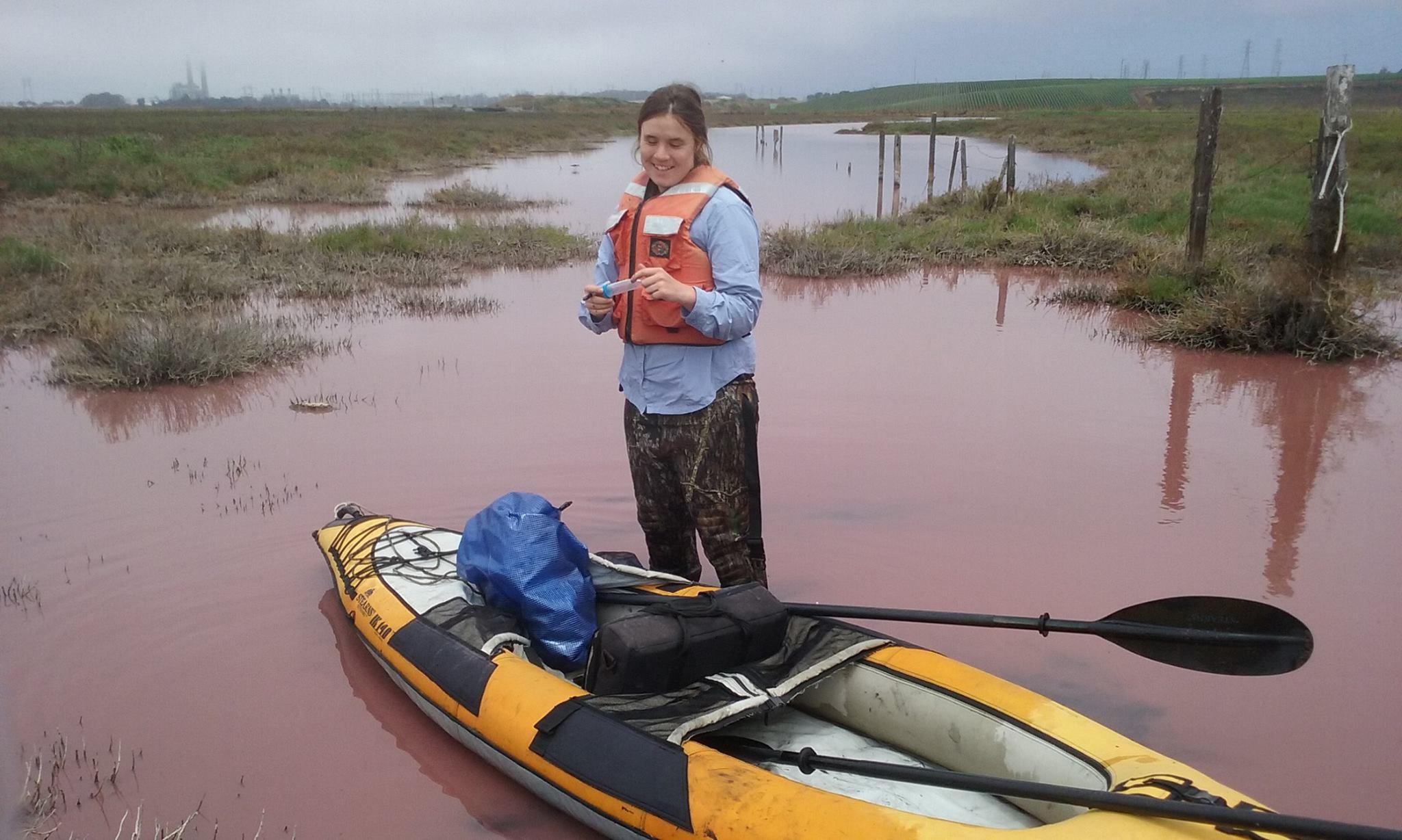 Miranda collecting water samples by kayak