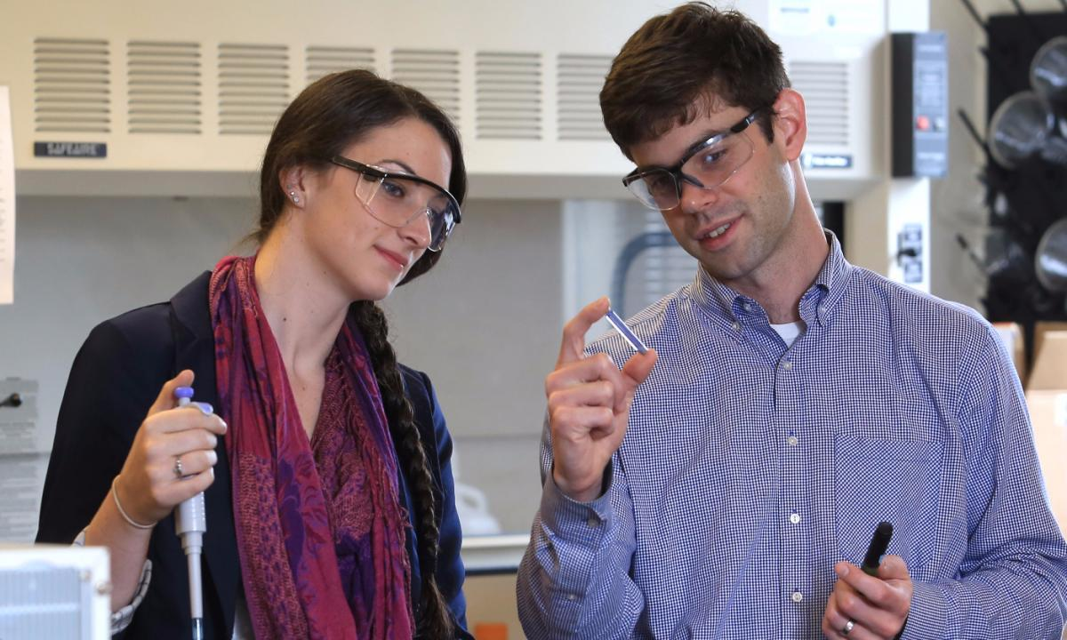 Student and assistant professor of chemistry, examine a vial of chemicals